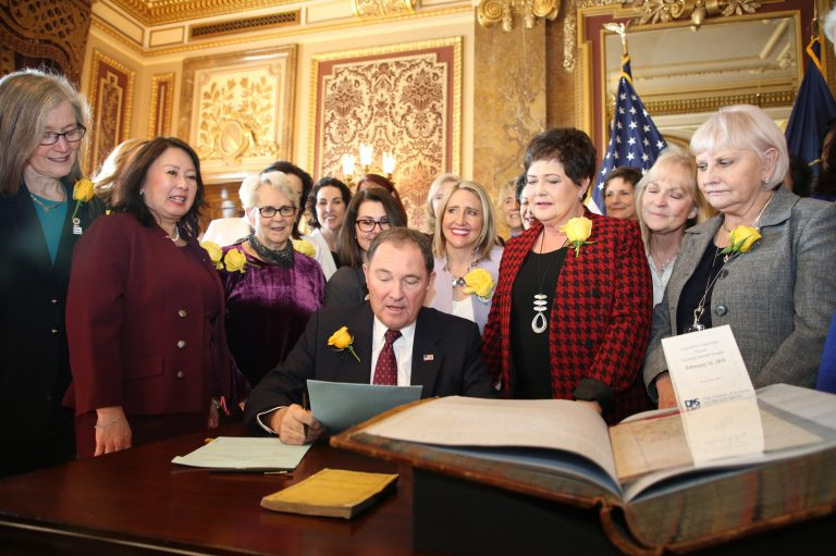 Utah Gov. Gary Herbert signs bill honoring the state's pioneering women suffragists on Wednesday. He's surrounded by state senators and representatives, and his wife, who are all wearing the yellow rose symbolizing suffrage. (Utah Governor's Office)