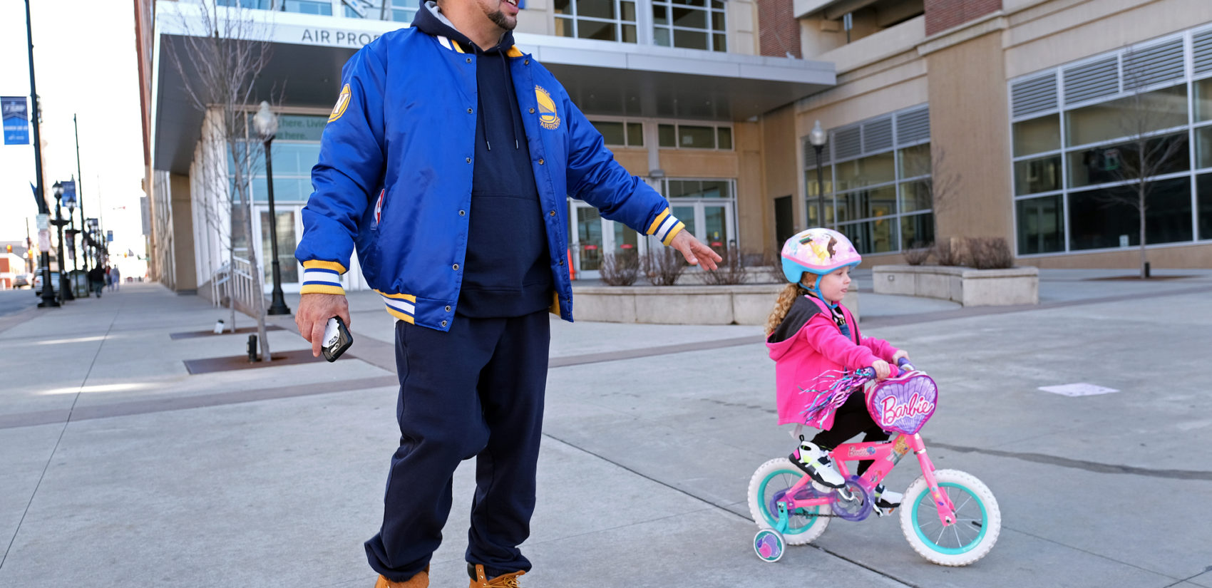 Edward Zayas, Jr., of Allentown, walks with his stepdaughter Avery Green, 4, as she rides her bike near the PPL Center in Allentown. Zayas is a chef at a bistro and has been working a lot to accommodate the increased demand for takeout and delivery orders.
