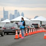 Cars line up at a drive through coronavirus test station in the parking lot at Citizens Bank Park. (Emma Lee/WHYY)