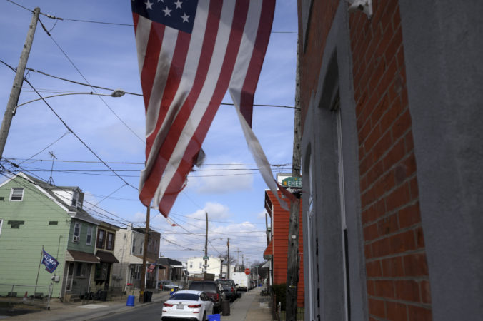 A torn American flag waves on a residential street in Bridesburg. (Bastiaan Slabbers for Keystone Crossroads)