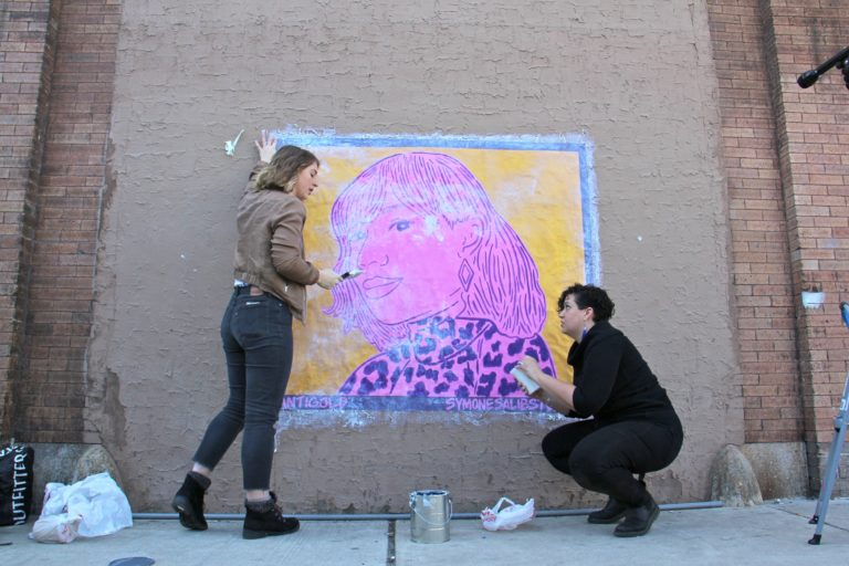 Nicole Nikolich (left) and Symone Salib install Salib's wheat paste portrait of Santigold on a wall of The Filmore. The work is one of 20 in the #SisterlyLove Project, celebrating 20 Philadelphia women during Women's History Month. (Emma Lee/WHYY)