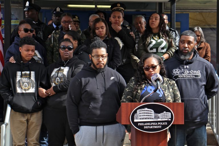 Shaki'ra Wilson Burroughs, backed by her extended family, speaks about the loss of her brother, Philadelphia Police Officer Robert Wilson, during a memorial ceremony on the fifth anniversary of his death. Wilson was shot to death by armed robbers at a video game store. (Emma Lee/WHYY)