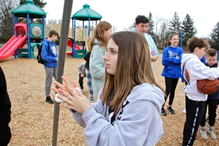 Tamanend Middle School student Brianna Muntz, 14,  uses a disposable hand wipe as she plays with friends on the Titus Elementary School playground. Both schools were closed, along with three others in Central Bucks County, as a precaution against the spread of COVID-19. (Emma Lee/WHYY)