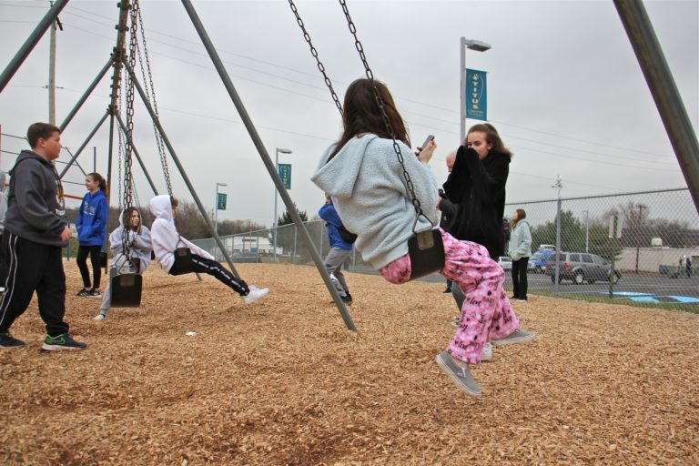 Children gather on the playground at Titus Elementary School, playing and talking to news reporters about the threat of the virus that shut down their school and four others in Central Bucks County. (Emma Lee/WHYY)