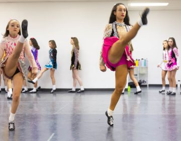 Dancers from the McDade-Cara School of Irish Dance warm up in their competition dresses for a dress rehearsal for the 2020 St. Patrick's Day Parade. (Emily Cohen for WHYY)