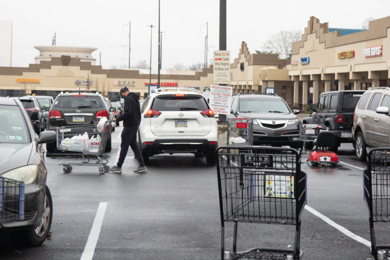 Carts litter the parking lot around 9 a.m. as a shopper heads back to their car with groceries after shopping at the ACME in Bala Cynwyd on March 19th 2020 during the uncertain times that surround the Covid 19 pandemic. (Emily Cohen for WHYY)