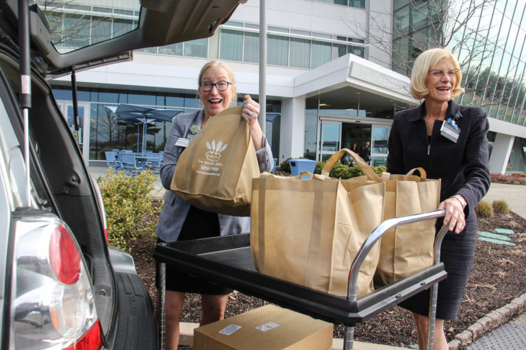 At Einstein Medical Center Montgomery, Chief Nursing Officer Annmarie Papa (left) and Chief Operating Officer Beth Duffy accept a donation of bagels and croissants from Four Worlds Bakery. (Emma Lee/WHYY)