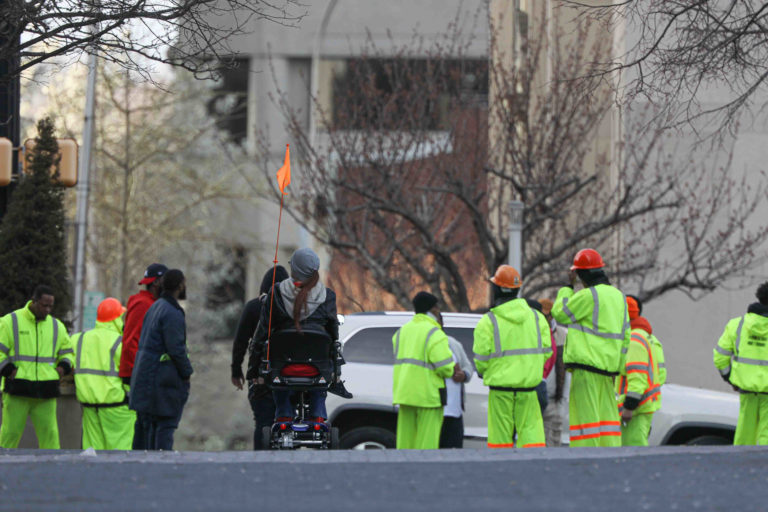 A pedestrian uses her scooter on Market Street in Wilmington, Del., as she approaches a group of construction workers on Thursday, March 26, 2020.  (Saquan Stimpson for WHYY)