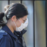 A woman walks on Market Street in Wilmington, Del., wearing a protective mask Friday March 27, 2020. (Saquan Stimpson for WHYY)