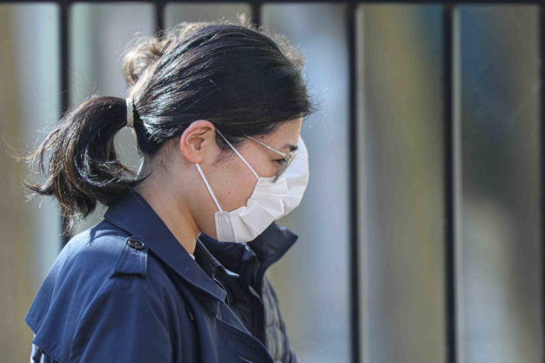 A woman walks in Wilmington, Del., wearing a protective mask