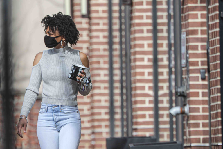 Keona Berry walks down Market Street with a protective mask on her face on Friday, March 27, 2020, in Wilmington, Del. (Saquan Stimpson for WHYY)