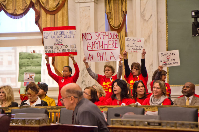 A coalition of South Philadelphia residents cheer opponents of safe injections sites at a hearing in City Council. (Kimberly Paynter/WHYY)