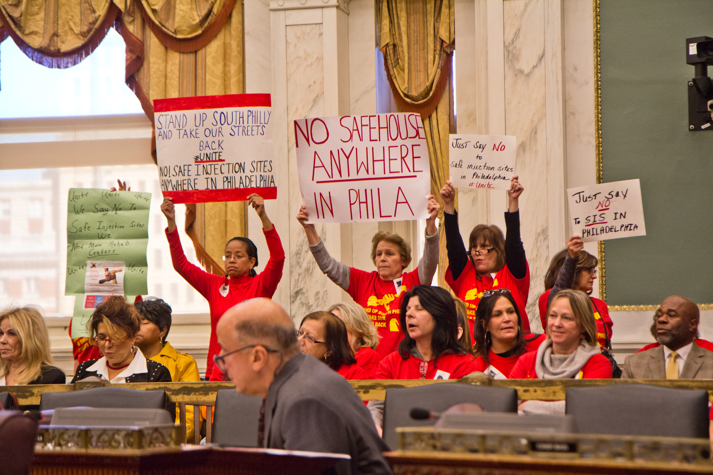 A coalition of South Philadelphia residents cheer opponents of safe injections sites at a hearing in City Council.