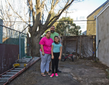 Adamarie Baez and Daniel Ortiz with their 10-year-old daughter Kaylee in the lot next to their home they've maintained and gardened in for years. (Kimberly Paynter/WHYY)