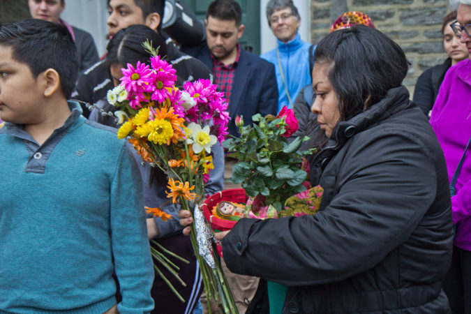 Carmela Apolonio Hernandez, a mother living in sanctuary at the Germantown Mennonite church, receives flowers from Suyapa Reyes. (Kimberly Paynter/WHYY)