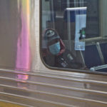 A SEPTA rider dons a surgical mask. (Kimberly Paynter/WHYY)