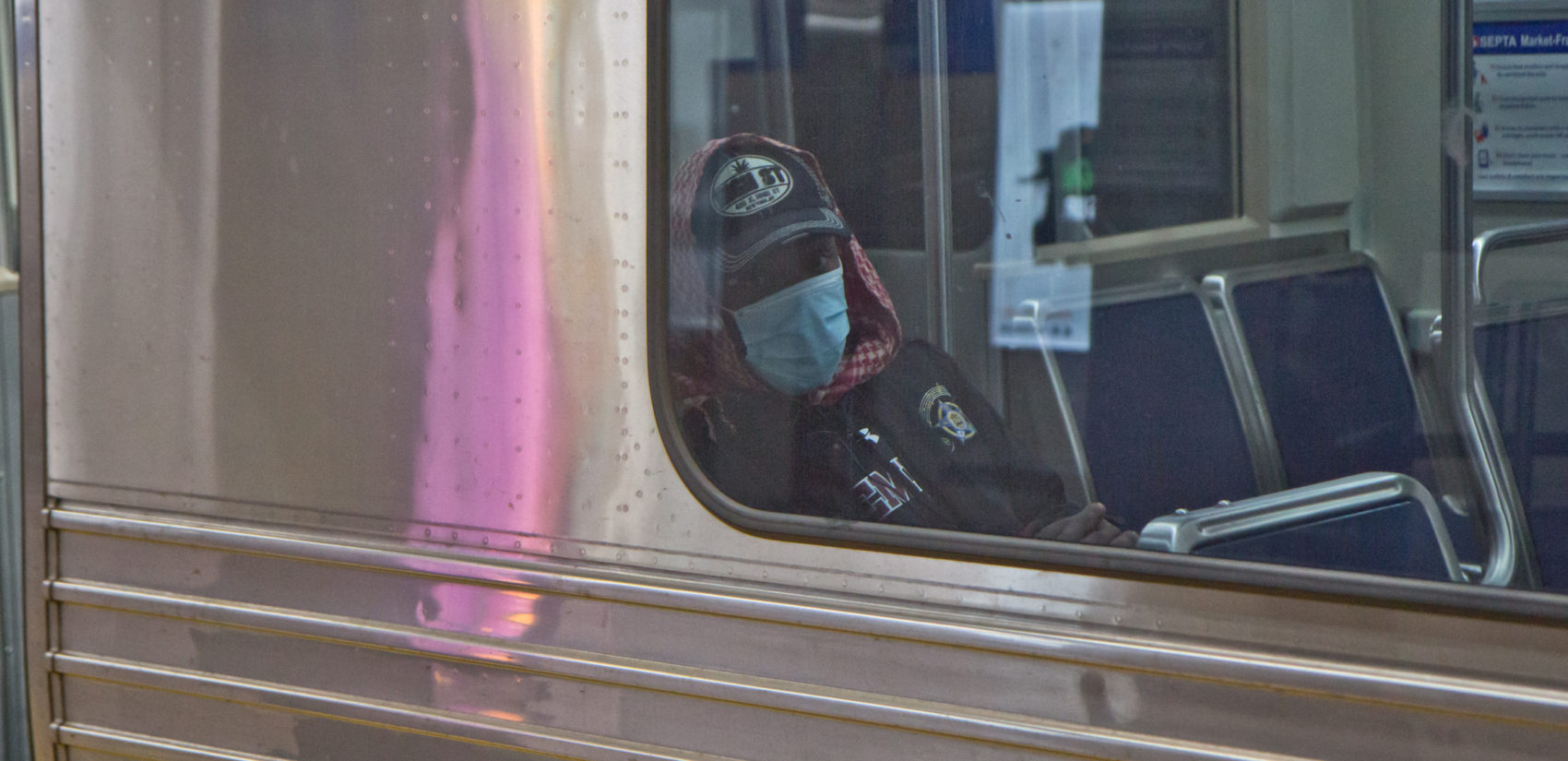 A subway rider in Philadelphia dons a surgical mask. (Kimberly Paynter/WHYY)