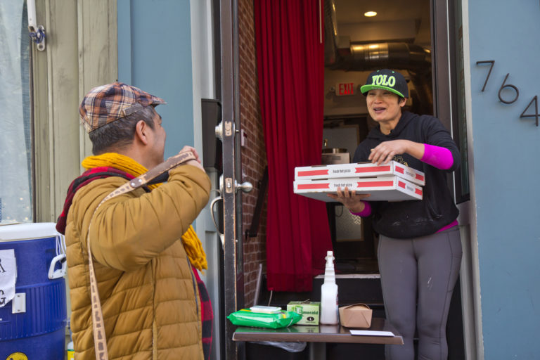 Kalaya owner Nok Suntaranon (right) hands out donated pizza to community members in need. (Kimberly Paynter/WHYY)