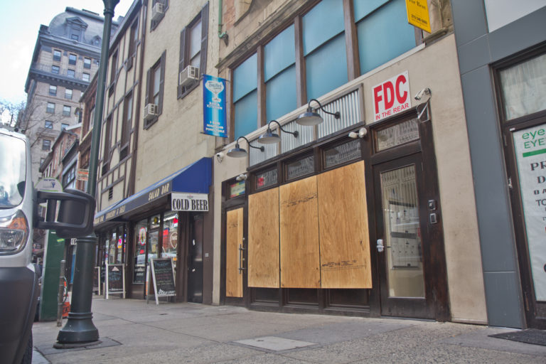 Businesses on Walnut Street in Center City Philadelphia are boarded up during non-essential business shutdown orders aimed to slow the spread of COVID-19. (Kimberly Paynter/WHYY)