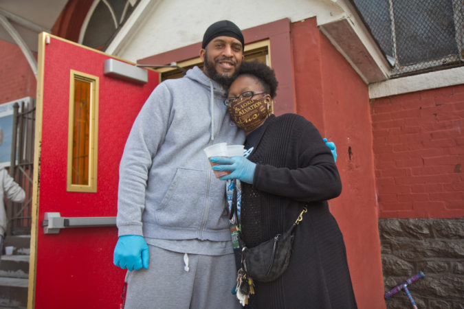 Javon Kinnard (left) and Serena Poindexter, members of the New Kingdom Baptist Church in Kensginton, have been volunteering to hand out meals to people in need. (Kimberly Paynter/WHYY)