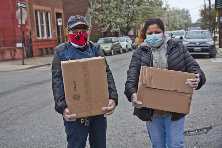 Noelia Ramírez and her daughter Carmen Arroyo, a factory worker, picked up boxes of free food during the coronavirus shutdowns that have students out of schools and workers unemployed. (Kimberly Paynter/WHYY)