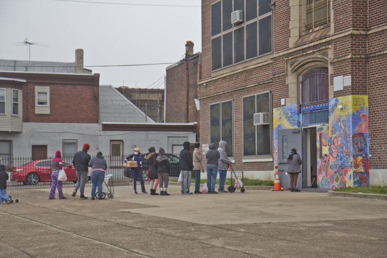 Hungry residents wait in line to pick up free food from the city Monday at Aspira Charter Stetson in Philadelphia. (Kimberly Paynter/WHYY)