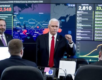 A monitor displaying a map of Asia and a tally of total coronavirus cases, deaths, and recovered, is visible behind Vice President Mike Pence, center, and Health and Human Services Secretary Alex Azar, left, as they tour the Secretary's Operations Center following a coronavirus task force meeting at the Department of Health and Human Services, Thursday, Feb. 27, 2020, in Washington. (AP Photo/Andrew Harnik)