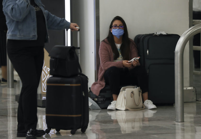 A woman wears protective masks as a precaution against the spread of the new coronavirus at the airport in Mexico City, Friday, Feb. 28, 2020. (Marco Ugarte/AP Photo)