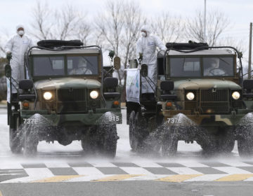 South Korean army trucks spray disinfectant as a precaution against the coronavirus on a street in Ulsan, South Korea, Tuesday, March 3, 2020. China's coronavirus caseload continued to wane Tuesday even as the epidemic took a firmer hold beyond Asia, with three countries now exceeding 1,000 cases and the U.S. reporting its sixth death. (Kim Young-tae/Yonhap via AP)