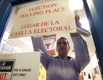 Dallas County election worker Maxx Nunez tapes up a sign before polls open for Super Tuesday voting at John H. Reagan Elementary School in the Oak Cliff section of Dallas, Tuesday, March 3, 2020. (AP Photo/LM Otero)