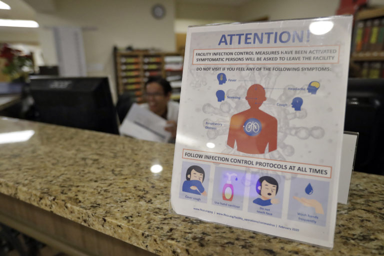 An infection Control Protocol poster sits on a nursing station desk at the Palm Garden of Tampa Health and Rehabilitation Center Thursday, March 5, 2020, in Tampa, Fla. (Chris O'Meara/AP Photo)