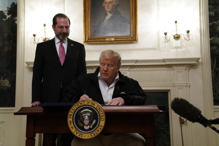 President Donald Trump signs an $8.3 billion bill to fight the coronavirus outbreak in the U.S., Friday, March 6, 2020 at the White House in Washington, as Department of Health and Human Services Secretary Alex Azar, looks on. The legislation provides federal public health agencies with money for vaccines, tests and potential treatments and helps state and local governments prepare and respond to the threat. The rapid spread of the virus has rocked financial markets, interrupted travel and threatens to affect everyday life in the United States. (AP Photo/Evan Vucci)