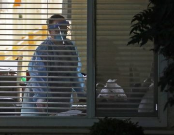 A worker wearing protective gear is seen through a window as she works in the room of Susan Hailey, 76, who has tested positive for the new coronavirus, Tuesday, March 10, 2020, at the Life Care Center in Kirkland, Wash., near Seattle. (AP Photo/Ted S. Warren)