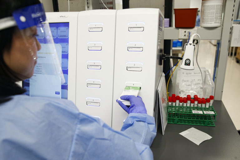 A laboratory technician prepares COVID-19 patient samples for semi-automatic testing at Northwell Health Labs, in Lake Success, N.Y. (John Minchillo/AP Photo)