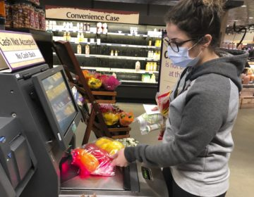 Wearing a surgical mask, Melissa Hall checks out of a Wegmans supermarket, Friday, March 13, 2020 in King of Prussia, Pa. (Michael Rubinkam/AP Photo)