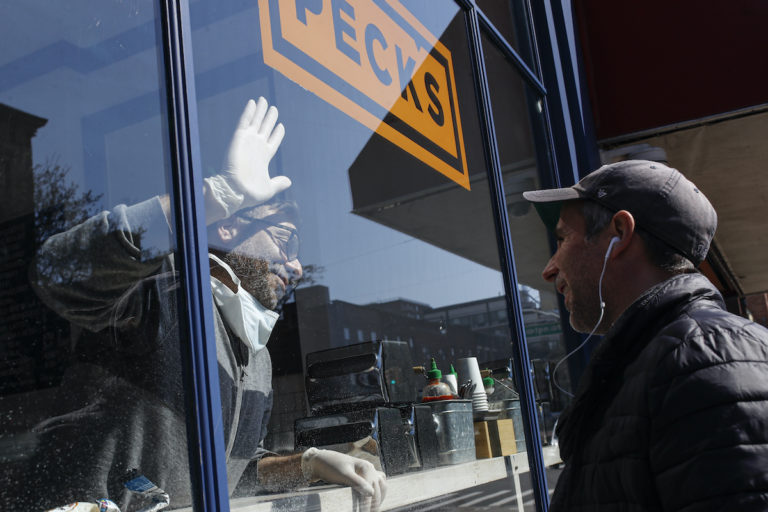 Peck's Food owner Theodore Peck touches hands with a customer through window glass while closing his storefront due to the coronavirus outbreak, Wednesday, March 18, 2020, (AP Photo/John Minchillo)