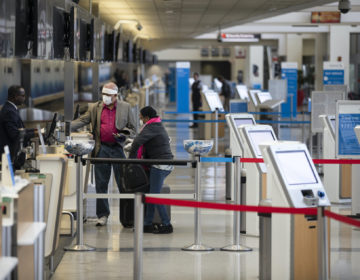 Passengers wearing face masks check in at Philadelphia International Airport in Philadelphia, Thursday, March 19, 2020. (Matt Rourke/AP Photo)