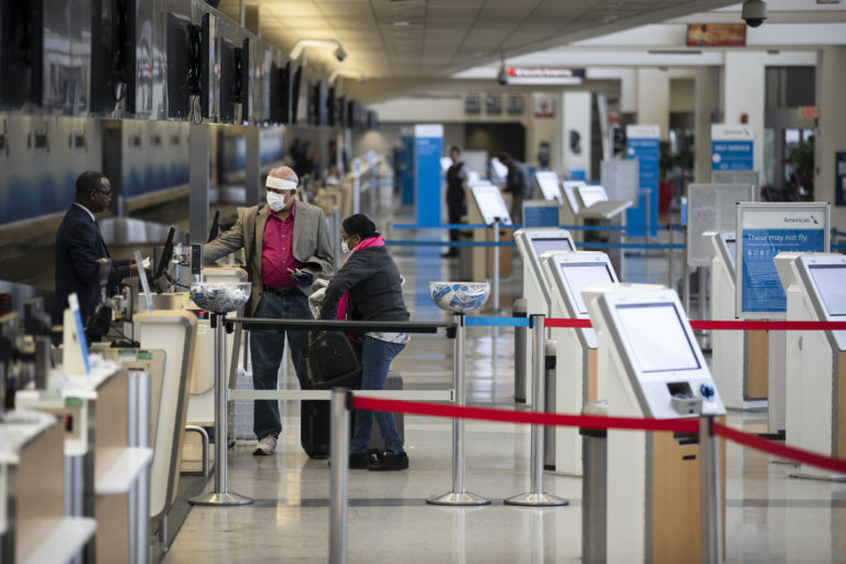 Passengers wearing face masks check in at Philadelphia International Airport in Philadelphia, Thursday, March 19, 2020. (Matt Rourke/AP Photo)