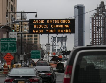 The Manhattan bridge is seen in the background of a flashing sign urging commuters to avoid gatherings, reduce crowding and to wash hands in the Brooklyn borough of New York.  (Wong Maye-E/AP Photo, file)