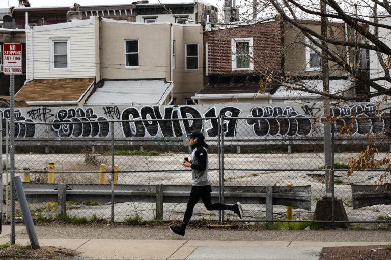 A jogger runs past a wall painted with the word