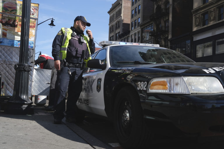 A Newark police officer uses his car megaphone to encourage social distancing at an intersection in Newark, N.J., Thursday, March 26, 2020. (AP Photo/Seth Wenig)