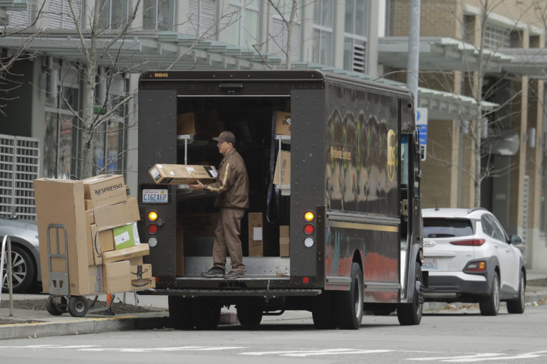 A United Parcel Service driver loads boxes during a delivery, Thursday, March 26, 2020, in downtown Seattle. UPS and other companies have been busy as people staying home under state-wide mandate amidst one of the worst outbreaks of the new coronavirus in the U.S. turn to online shopping to meet their needs. (AP Photo/Ted S. Warren)