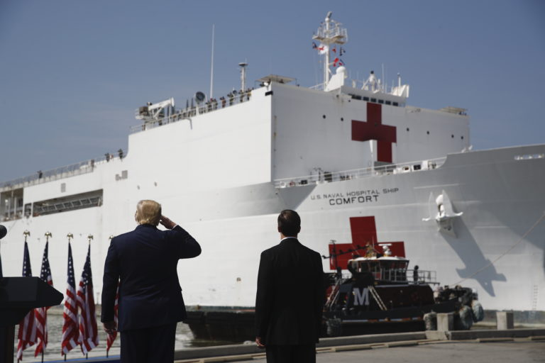 President Donald Trump salutes as the U.S. Navy hospital ship USNS Comfort pulls away from the pier at Naval Station Norfolk in Norfolk, Va. (Patrick Semansky/AP Photo)