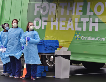 Nurses with ChristianaCare wait for the next person to be tested for coronavirus during a free drive-through area at the Riverfront complex in downtown Wilmington, Delaware on Friday, March 13, 2020.  (Butch Comegys for WHYY)
