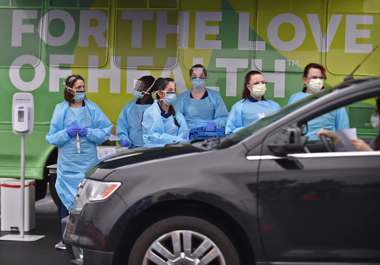 Nurses with Christiana Care wait for the next vehicle to arrive to test people for the coronavirus on Friday, March 13, 2020, at the Riverfront complex in downtown Wilmington, Delaware. The test was free. (Butch Comegys for WHYY)