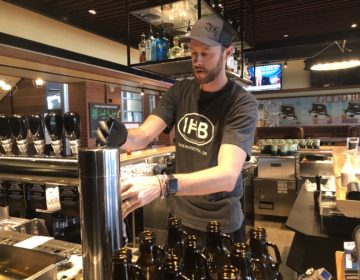 Dustin Mitchell fills up a growler for take-out orders at Iron Hill Brewery. (Cris Barrish/WHYY)