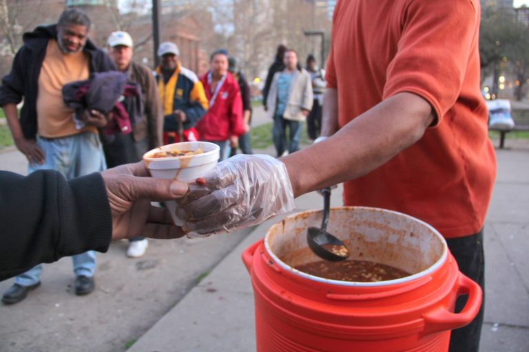 People line up for a meal in Pennypacker Park across from the Family Court building on Vine Street. (Emma Lee for WHYY)