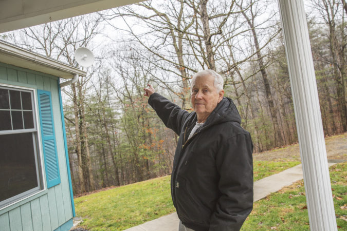 Ken Diven, a founding member of the cooperative and an early user of its service, points to the radio receiver at his home. It picks up signal from the radio tower and connects to a router inside. (Min Xian/Keystone Crossroads)