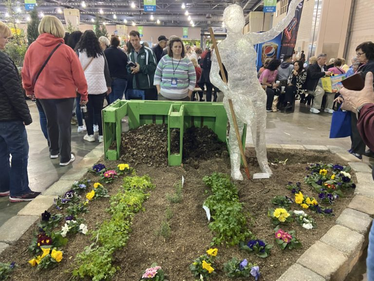 Teacher Nora Melley in front of the Lincoln High School exhibit at the Philadelphia Flower Show. (The Notebook)