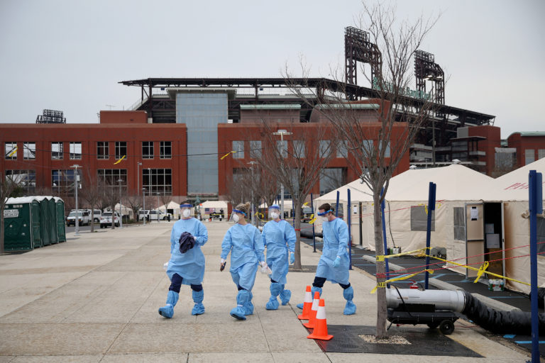 Philadelphia Medical Reserve Corps volunteers (from left) Megan Boyle, Marina Spitkovskaya, Jamie Huot, and Stephen Bonett, all of whom are nurses, walk to the swabbing tent as the city's coronavirus testing site prepared to open next to Citizens Bank Park in South Philadelphia on Friday, March 20, 2020. (Tim Tai/The Philadelphia Inquirer)